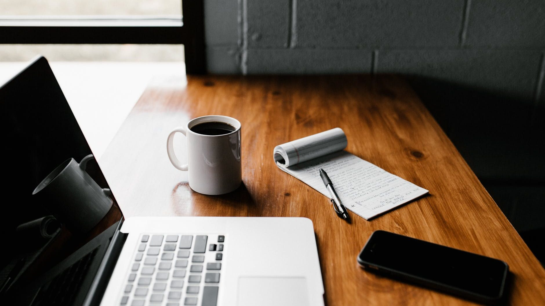 A wooden desk with a laptop, white mug full of coffee and a nitebook with a to do list